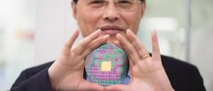 Professor Min Gu with the breakthrough nanophotonic chip that can harness the angular momentum of light. Photo: RMIT