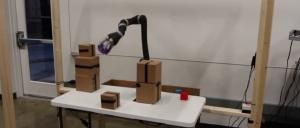 A robot picks up an object while navigating around piles of boxes. Image: Duke University