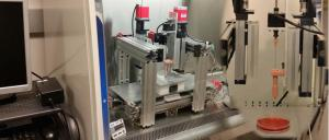 The image shows a multiarmed bioprinter used to 3-D print cartilage. A special nozzle for printing bioink composed of strands of cartilage can be seen.